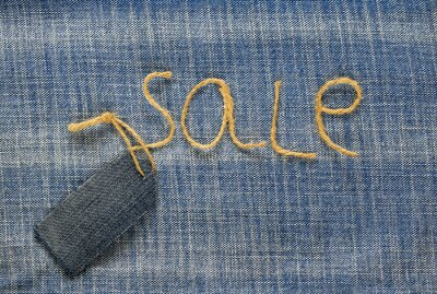 stylowe tkaniny denim tkaniny z napisem sprzedaży sznurka w mojej ręce i puste tag cena