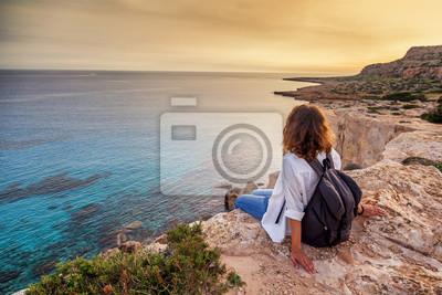 Plakat Stylowy młody podróżnik kobieta ogląda piękny zachód słońca na skałach na plaży, Cypr, Cape Greco, popularne miejsce na letnie podróże w Europie