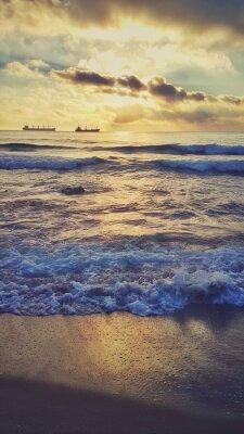 Plakat Sunrise ans rozpryskiwania fale na plaży
