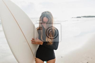Plakat Surfingowiec dziewczyna na plażowym mienie kipieli deski dopatrywania oceanie macha w słonecznym dniu. Prawdziwe szczęśliwe emocje młoda aktywna ładna kobieta przygotowywają surfować. Styl życia wakac
