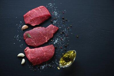 Plakat Surowe marbled steki mięsne z przyprawami, czarna powierzchnia drewniana