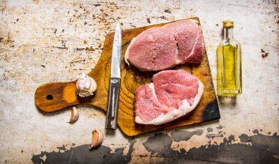 Plakat Surowe świeże mięso z czosnkiem i olej na desce.