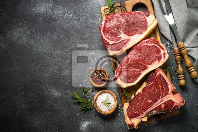 Plakat Surowego mięsa wołowiny stek na czarnym odgórnym widoku.