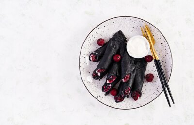 Sweet pancakes with ricotta and cherries. Black pancakes. Breakfast. Top view, copy space