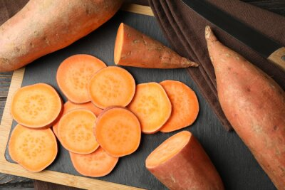 Plakat Sweet potato, board and towel on wooden background, top view