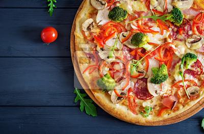 Świeża włoska pizza z filetem z kurczaka, pieczarkami, szynką, salami, pomidorami, serem dalej na czarnym tle. Włoskie jedzenie. Widok z góry.