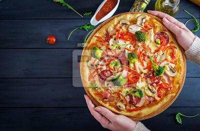 Świeża włoska pizza z filetem z kurczaka, pieczarkami, szynką, salami, pomidorami, serem na czarnym tle w rękach. Włoskie jedzenie. Widok z góry