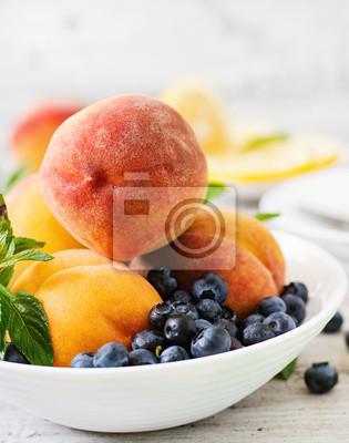 Świeże brzoskwinie i jagodami w misce na jasnym drewnianym tle rustykalnym stylu