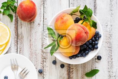 Świeże brzoskwinie i jagody w misce na jasnym tle drewnianych w stylu rustykalnym. Widok z góry