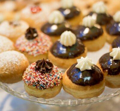 Plakat Świeże pączki z dżemem i czekoladą w piekarni w rynku w czasie żydowskiego święta Chanuki.