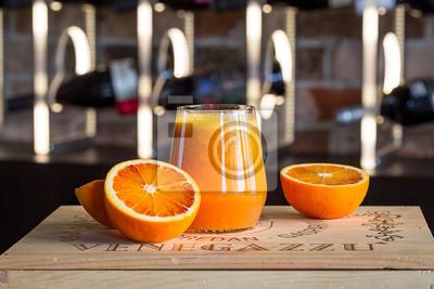 Plakat Świeże Sok pomarańczowy i owoce na drewnianych pudełku, rozmazany tła światła