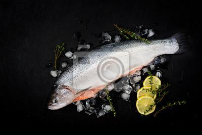Świeże surowe łososia czerwone ryby z lodem na ciemnym tle. Płaskie leże. Widok z góry
