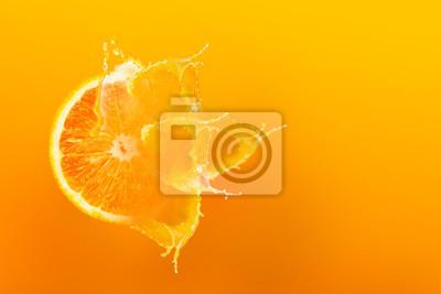 Plakat Świeży połówka plasterek dojrzały pomarańczowy owocowy floation z pluśnięcie kroplą na soku pomarańczowym z kopii przestrzenią