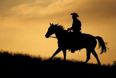 Plakat Sylwetka kowboj i koń idzie się łąki z pomarańczowym i żółtym tle nieba.