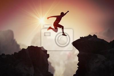 Plakat Sylwetka skacze nad górami i falezami przy zmierzchem młody człowiek.