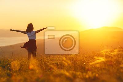 Plakat Szczęśliwa kobieta, stojąca z plecami na zachód słońca w przyrodzie iwith otwarte ręce.