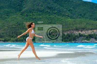 Szczęśliwa kobieta wzdłuż białej plaży