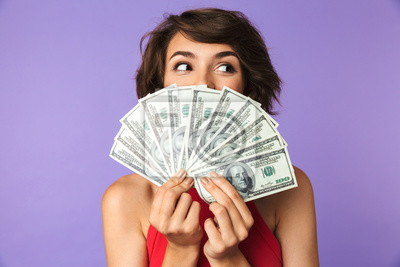 Plakat Szczęśliwa Ładna brunetki kobieta zakrywa jej twarz z pieniądze