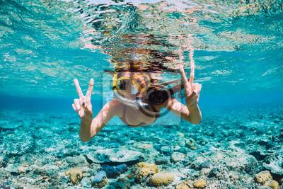 Plakat Szczęśliwa młoda kobieta pływa pod wodą w tropikalnym oceanie