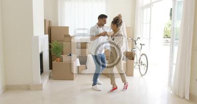 Plakat Szczęśliwa młoda para świętuje przeprowadzki tańczyć razem w salonie otoczony pakowania pudełek