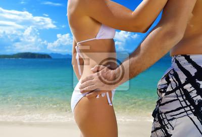 Plakat Szczęśliwa para stoi ramię w ramię na plaży na brzegu