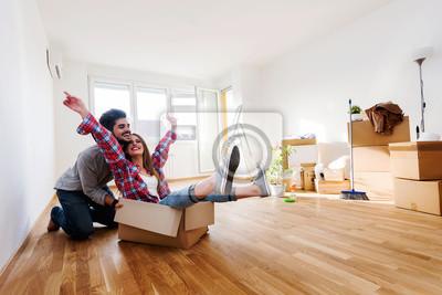 Plakat Szczęśliwej pary młodych przenoszenie w nowym domu rozpakowaniu pola