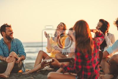 Plakat Szczęśliwi przyjaciele siedzi na plażowym śpiewie i bawić się gitarę podczas zmierzchu