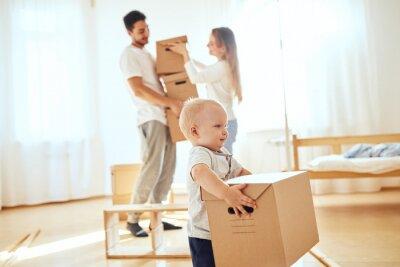 Plakat Szczęśliwy chłopiec przewożenie rusza się pudełko, rodzice na zamazanym tle. Przenoszenie koncepcji