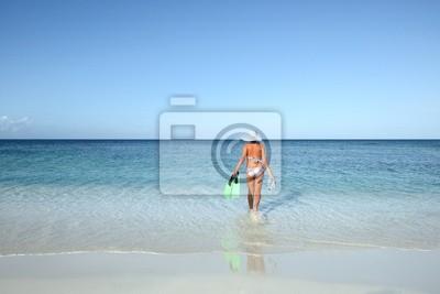Szczupła kobieta w bikini idzie pływać