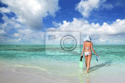 Plakat Szczupła kobieta w bikini idzie pływać w morzu