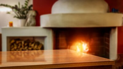Table background of free space and blurred home interior with fireplace