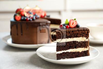 Plakat Talerz z plasterkiem ciasto czekoladowe gąbki jagodowe na szary stół