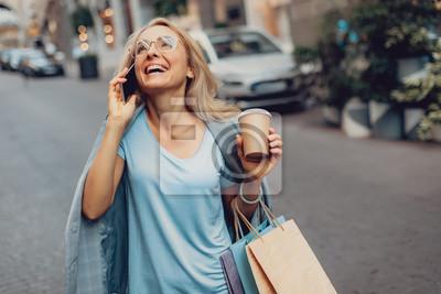 Plakat Talia w górę portreta rozochocona dama w średnim wieku opowiada na telefonie komórkowym na ulicie w szkłach. Ona trzyma filiżankę kawy i torby na zakupy
