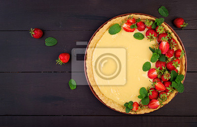 Tart with strawberries and whipped cream decorated with mint leaves on dark background. Top view