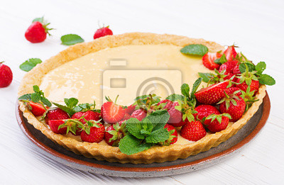 Tart with strawberries and whipped cream decorated with mint leaves on light background.
