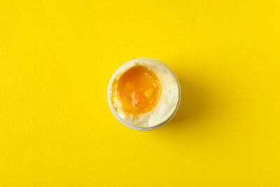 Plakat Tasty boiled egg on yellow background, top view