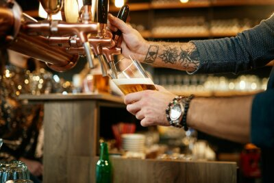 Plakat Tattooed caucasian barman pouring beer while standing in pub. Selective focus on hand.