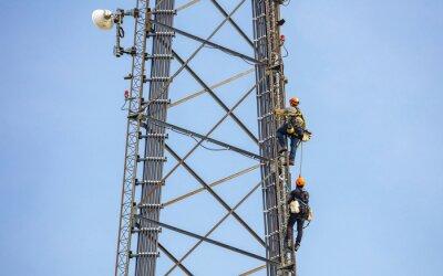 Plakat Telecom maintenance. Two repair men climbing on tower against blue sky background
