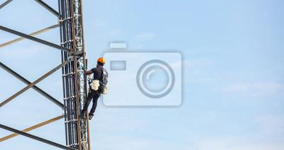 Plakat Telecom maintenance. Worker climber on tower against blue sky background