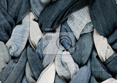 textured background of a variety of denim and pants in various shades of blue intertwined in braids