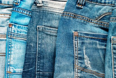 textured background of a variety of denim pants in various shades of blue stacked in rows