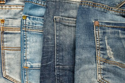textured background of a variety of denim pants in various shades of blue stacked rows of back pockets up