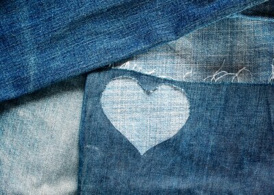 textured background of many denim pieces of different shapes and shades of blue