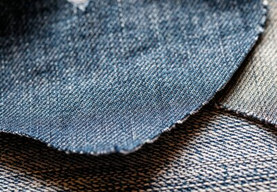 textured background of various scraps of fabric in the heart shape of denim lies on the blue fabric