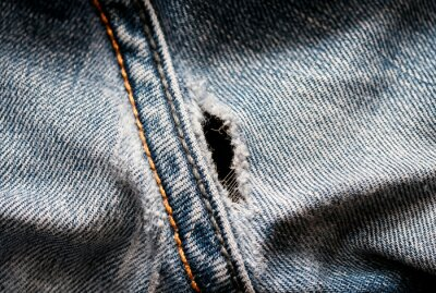textured background with hole on blue denim pants