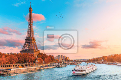 Plakat The main attraction of Paris and all of Europe is the Eiffel tower in the rays of the setting sun on the bank of Seine river with cruise tourist ships