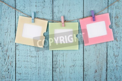 Plakat Three empty colorful photo frames or notes paper hanging with clothespins on wooden blue vintage shabby chic background