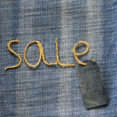 tkanina dżinsowa w tle z napisem sprzedaż sznurka w ręku i metką pustą