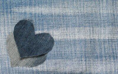 tło dwóch serc drelichowych leżą na modnej teksturowanej niebieskiej tkaniny