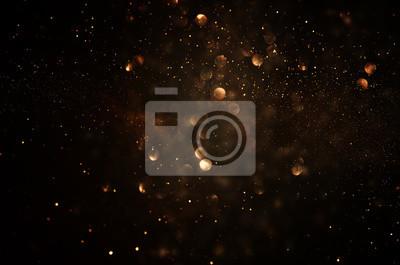 Plakat tło wzór światła świecidełka. ciemne złoto i czerń. de focused.